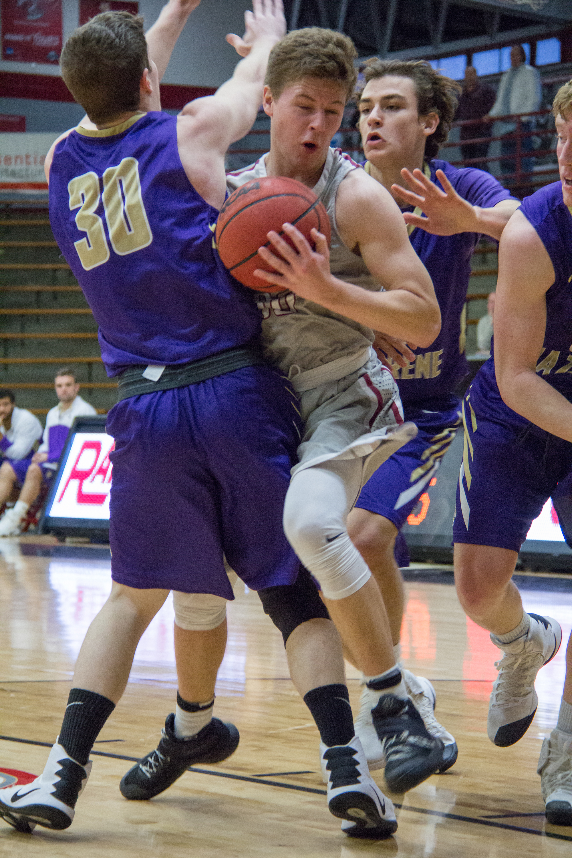 Junior Guard Eric Davidson tries to get through two defenders in the win against Olivet Nazarene on Dec. 10. Photo by Jennifer Ulery