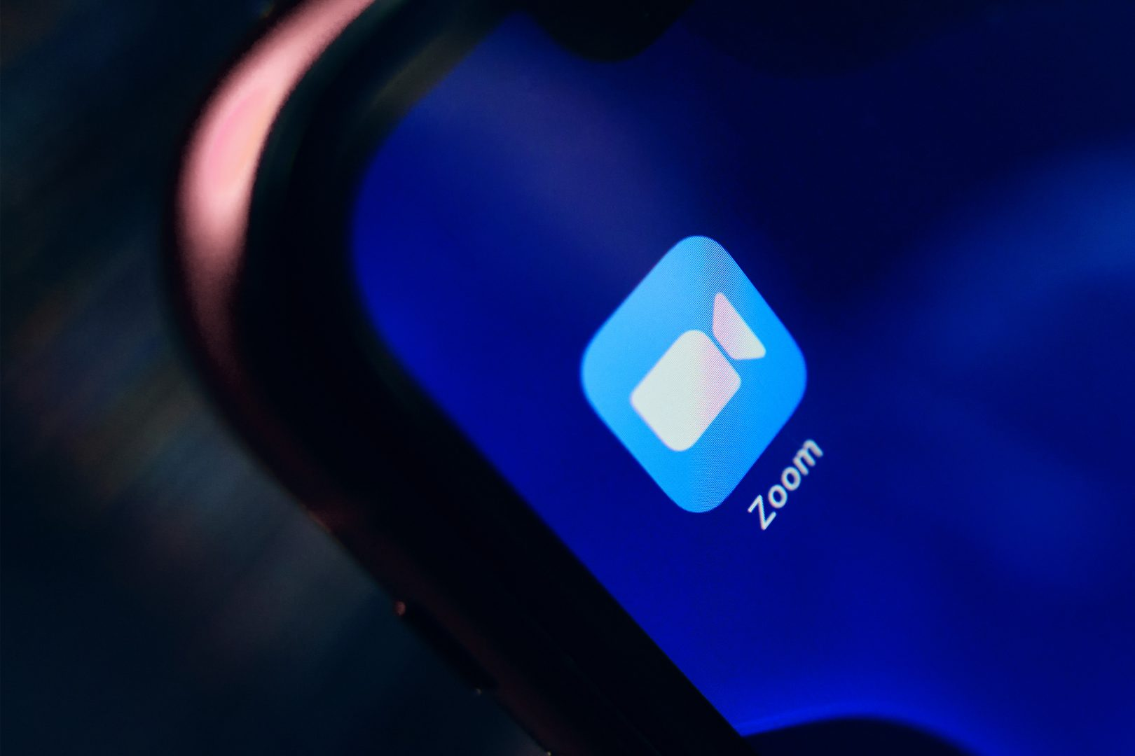 The app icon for the video-conferencing app Zoom is featured on a phone screen held in the hand of an unknown person.