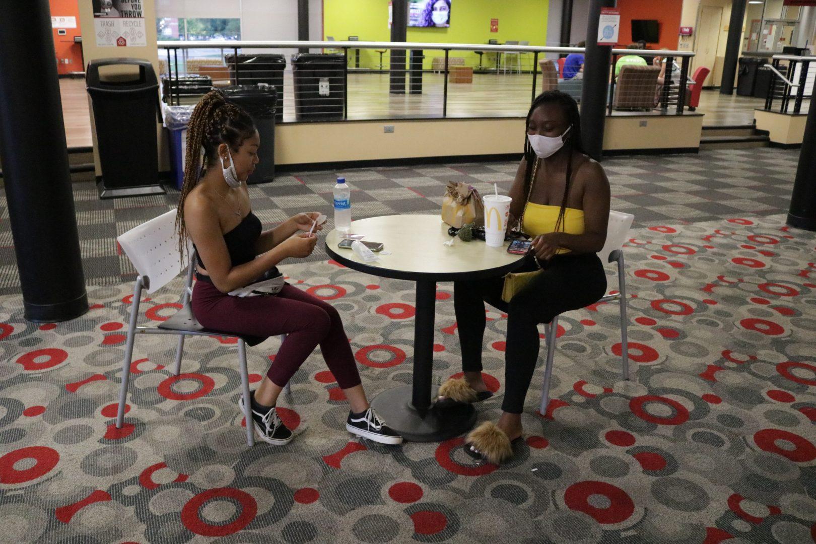 Sophomore psychology major Desiree Legree and sophomore exercise science major Gerri Bonner eat inside in Schwitzer Student Center while wearing masks on Sept. 13.