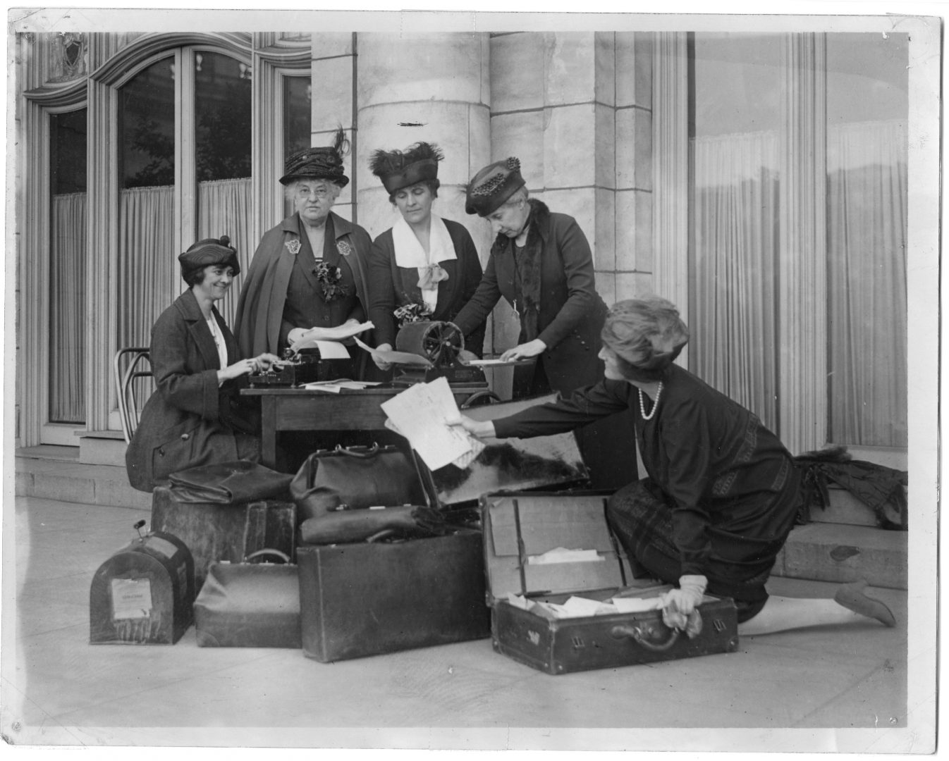 Five suffragists, including Marie Stuart Edwards (middle), a women's rights activist and reformer from Peru, Indiana, stand at a desk on the sidewalk with luggage during their western tour on behalf of the women's suffrage movement.