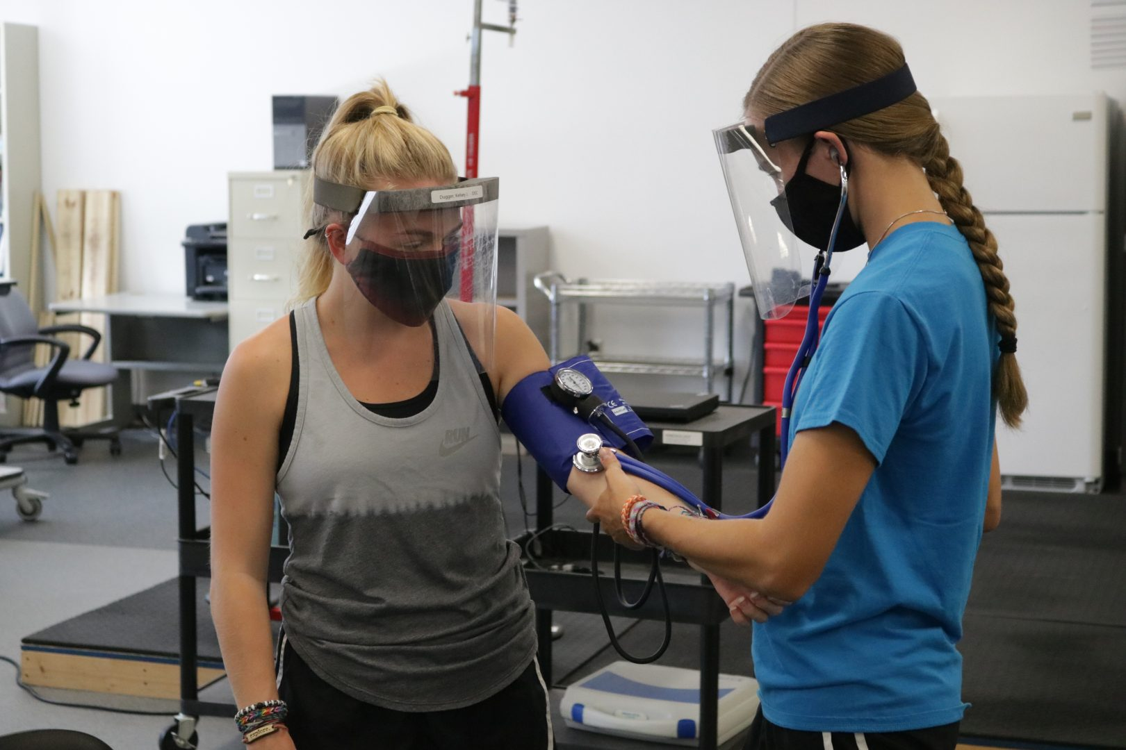 Junior exercise science major Melissa Spencer takes the blood pressure or her classmate junior and exercise science major Kelsey Dugger. Although their class meets in person, they are required to wear full PPE with face masks and face shields while in the classroom.